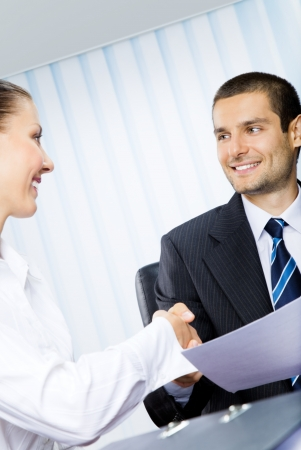 Two happy businesspeople, or businessman and client, with document at office photo