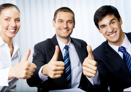 thumbs up gesture: Happy smiling successful gesturing businesspeople at office. Focus on hands.