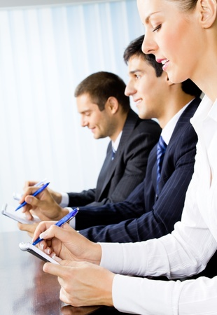 Three happy smiling businesspeople at meeting, presentation or conference Stock Photo - 8773390