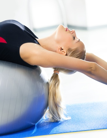 haciendo ejercicio: Feliz sonriente joven en ropa deportiva, haciendo ejercicio de fitness con fit ball, en el interior