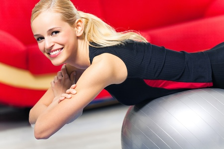 Portrait of young happy smiling woman in sportswear, doing fitness exercise with fit ball, indoors photo