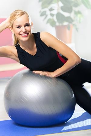 haciendo ejercicio: Retrato de una joven mujer sonriente feliz en ropa deportiva, haciendo ejercicio de fitness con fit ball, en el interior Foto de archivo