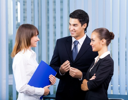 Three young happy businesspeople at office Stock Photo - 8876755