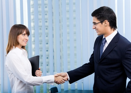 Two happy businesspeople, or businessman and client, with document at office Stock Photo - 8876812