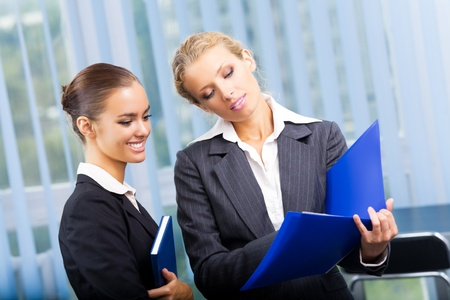 Two happy smiling businesswomen working with documents at office photo