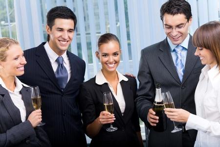 personas celebrando: Feliz sonrientes j�venes empresarios celebrando con champ�n en Oficina Foto de archivo