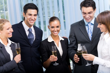 Happy smiling young businesspeople celebrating with champagne at office photo