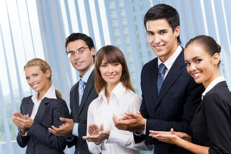Happy businesspeople applauding at office photo