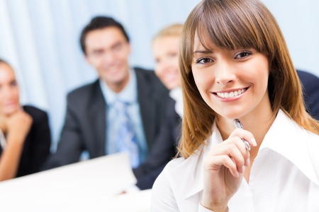n�gocier: Portrait de femme d'affaires souriant heureux et coll?gues sur le fond, au bureau Banque d'images
