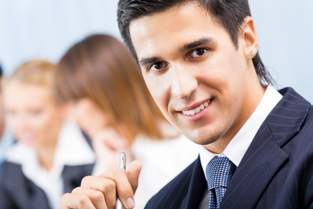 meet: Portrait of happy smiling businessman and colleagues on background, at office Stock Photo