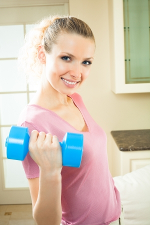 Portrait of young happy smiling woman in sportswear, doing fitness exercise with dumbbell, indoors Stock Photo - 8951080
