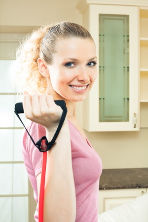espander: Portrait of young woman in sportswear, doing fitness exercise with expander, indoors