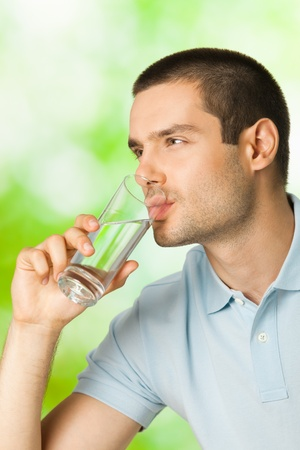 health drink: Young man drinking water, outdoors Stock Photo
