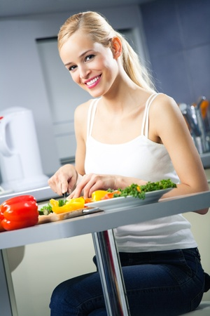 Young happy woman making salad at domestic kitchen photo