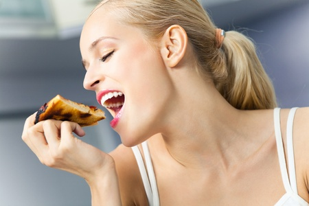 Young happy woman eating pizza, indoors photo