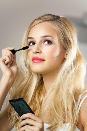 Portrait of young smiling woman applying mascara at home photo