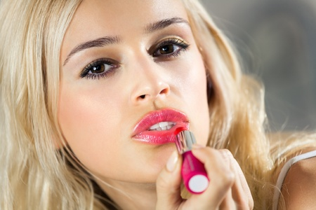 wellfare: Portrait of young woman applying lipstick at home Stock Photo