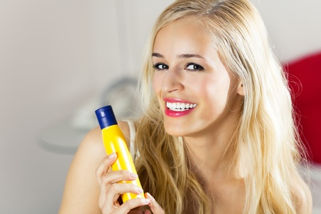 Young beautiful smiling woman with moisturizer, at home photo