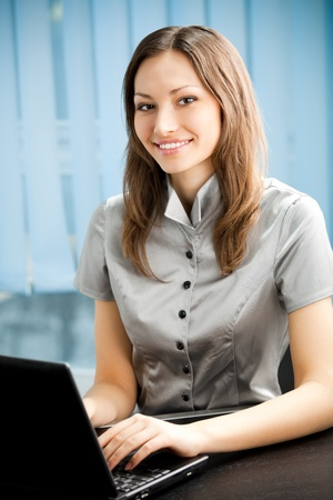 social worker: Portrait of successful happy smiling businesswoman working with laptop at office