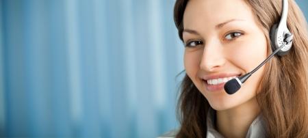slogan: Retrato de feliz sonriente operadora de telefon�a de apoyo en el auricular en el lugar de trabajo. Para proporcionar la m�xima calidad, he hecho esta imagen por la combinaci�n de dos fotos. Puede utilizar la parte izquierda de lema, texto o banner. Foto de archivo
