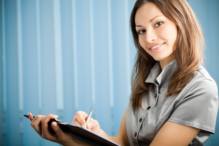 sign contract: Portrait of writing happy smiling businesswoman working at office. You can use left part for slogan, big text or banner. Stock Photo
