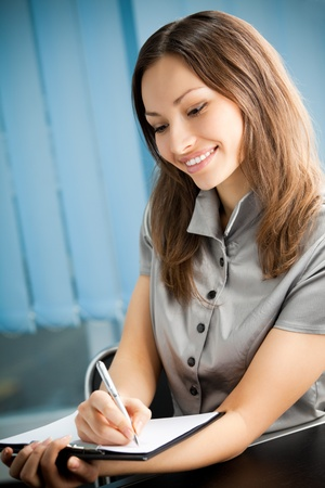 Portrait of writing happy smiling businesswoman working at office Stock Photo - 9037021