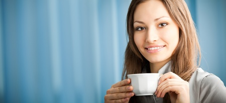 part i: Portrait of beautiful young happy smiling businesswoman drinking coffee at office. To provide maximum quality, I have made this image by combination of two photos. You can use left part for slogan, big text or banner. Stock Photo