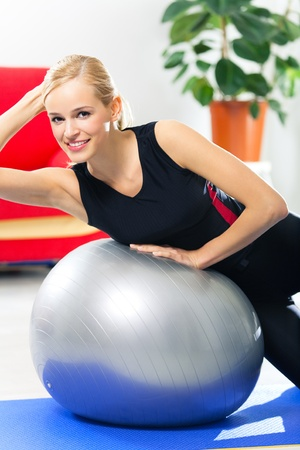 Portrait of young happy smiling woman in sportswear, doing fitness exercise with fit ball, indoors Stock Photo - 9098144