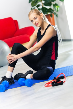 Portrait of young woman in sportswear with dumbbell and expander at home photo