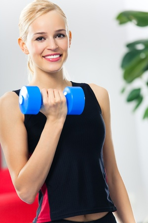 Portrait of young woman in sportswear, doing fitness exercise with dumbbell, indoors photo