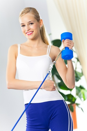 Portrait of young woman in sportswear, doing fitness exercise with dumbbell and expander at home photo