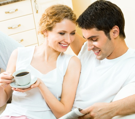 Young happy amorous couple reading newspaper at home Stock Photo - 9153192