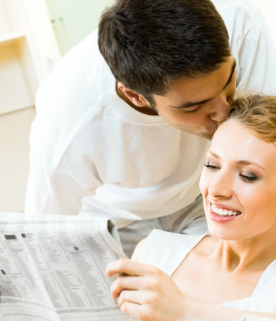 Young happy amorous couple reading newspaper at home Stock Photo - 9153191