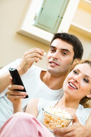 pareja viendo tv: Joven pareja comiendo palomitas de ma�z y viendo la televisi�n juntos en casa Foto de archivo