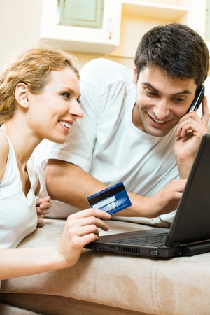 Young happy smiling couple with laptop, paying by credit card in internet store, at home photo