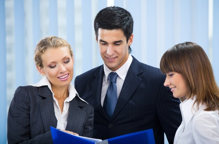 Three young happy businesspeople at office Stock Photo - 9324292