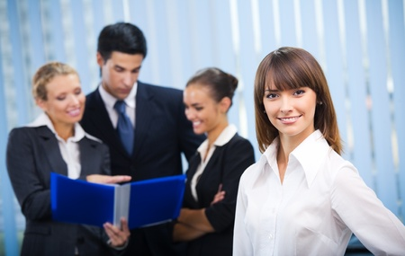 corporate group: Portrait of happy smiling businesswoman and colleagues on background, at office