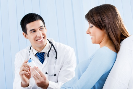 Happy young doctor with medical drug and female patient at office photo