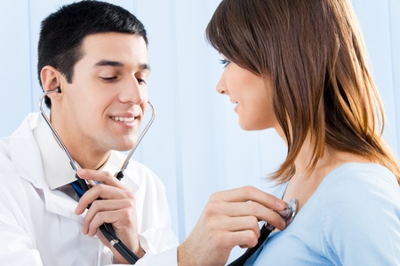 Doctor with stethoscope and female patient Stock Photo - 9340529