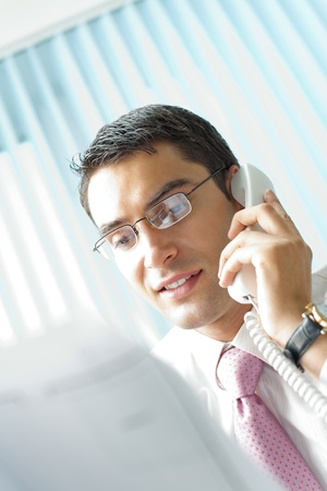 Businessman with phone and document at office photo