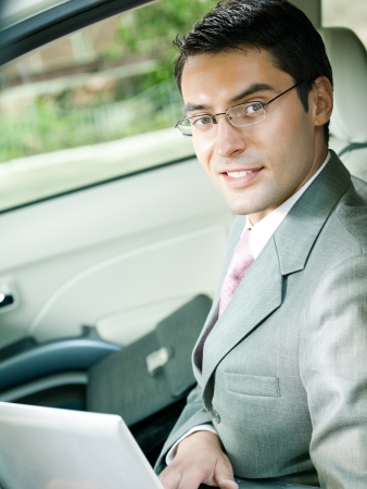 tecnology: Portrait of happy businessman with laptop in car