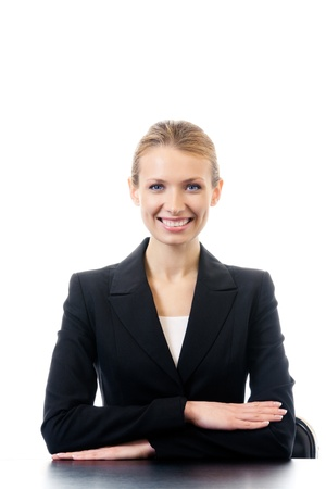 Portrait of happy sitting; smiling businesswoman at workplace, isolated on white background photo
