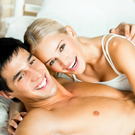 Young attractive happy smiling couple at bedroom photo