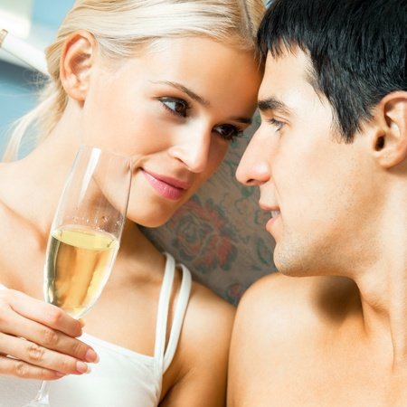 Young happy couple with champagne at bedroom photo