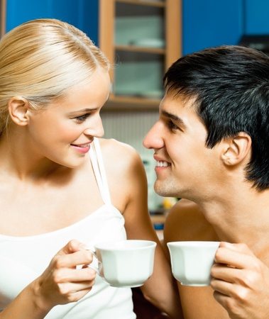 hot date: Young happy smiling couple drinking coffee together at home