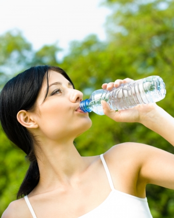 girl drinking water: Young woman drinking water at workout, outdoors Stock Photo