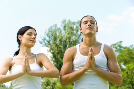 Young couple doing yoga moves, meditating or praying together, outdoors  photo