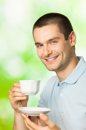 hombre tomando cafe: Retrato de hombre sonriente feliz beber café, al aire libre Foto de archivo