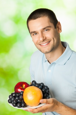 Portrait of young happy smiling man with plate of fruits, outdoors