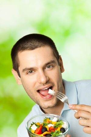 eating area: Portrait of young happy man eating salad, outdoors. You can use top part for slogan or text.  Stock Photo